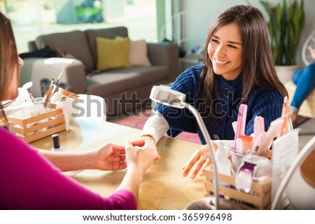 Gorgeous young woman getting her nails done by a manicurist in a beauty salon - stock photo