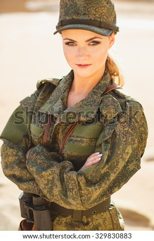 Gorgeous young woman in a Military costume on the background of a dessert