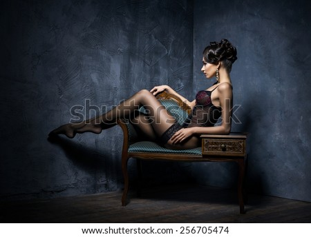 Gorgeous young woman in sexy lingerie and stockings posing in a vintage interior. - stock photo