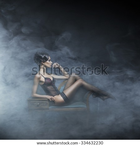 Gorgeous young woman in sexy lingerie and stockings posing in a vintage interior over smoky background. - stock photo