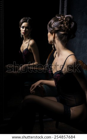 Gorgeous young woman in sexy lingerie and stockings posing in a vintage interior with a mirror. - stock photo