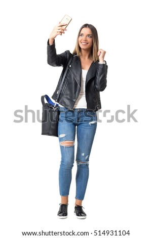 Gorgeous young woman in street style clothes taking selfie with mobile phone. Full body length portrait isolated over white background