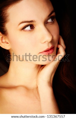 Gorgeous young woman in the dark touching her face