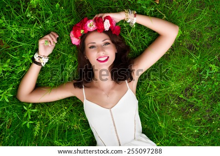 Gorgeous young woman in white dress with a flower wreath lying down on the grass. - stock photo