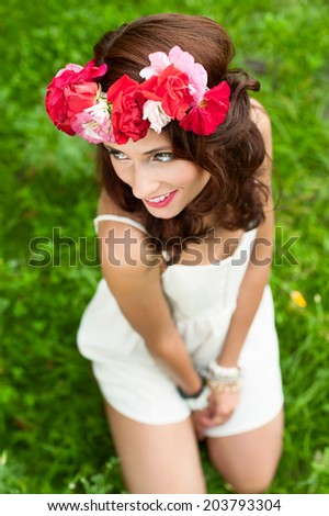 Gorgeous young woman  in  white dress with a flower wreath on her head. - stock photo