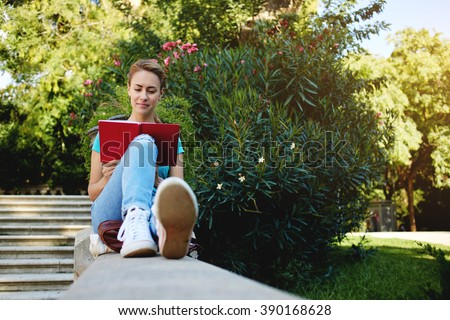 Gorgeous young woman is reading interesting book during her recreation time in summer weekend, attractive female student is preparing for college tuition while is sitting alone in beautiful green park - stock photo
