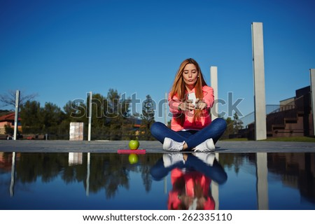 Gorgeous young woman making self portrait while holding up her smart phone, beautiful hipster girl take pictures of her self with cell phone, female teenager having fun in the park - stock photo