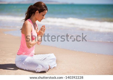 Gorgeous young woman meditating and practicing yoga at the beach - stock photo