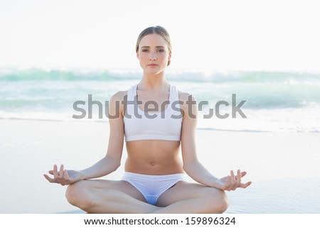 Gorgeous young woman meditating sitting on the beach looking at camera - stock photo