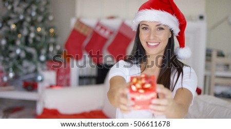 Gorgeous young woman offering an Xmas gift
