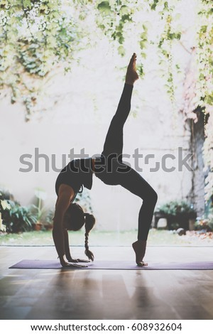 Gorgeous young woman practicing yoga indoor. Beautiful girl practice adkho-mukkha-shvanasana in a training hall.Calmness and relax, female happiness concept.Vertical, blurred background