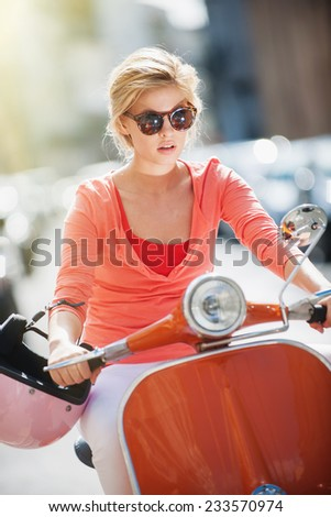 gorgeous young woman riding  a vintage scooter in the street, she has a topknot, sunglasses and a pink helmet - stock photo