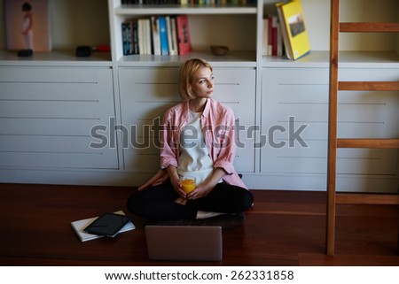Gorgeous young woman sitting at bookshelf on the floor with open laptop computer while she works with comfort from home, young business woman drink orange juice while having breakfast, young student - stock photo