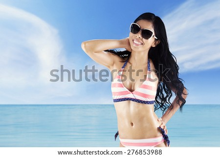 Gorgeous young woman standing on the coast while wearing swimwear and sunglasses