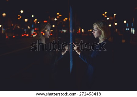 Gorgeous young woman touching digital display of smart modern bus station, female caucasian using city computer for touristic information while standing at night with urban lights on background - stock photo