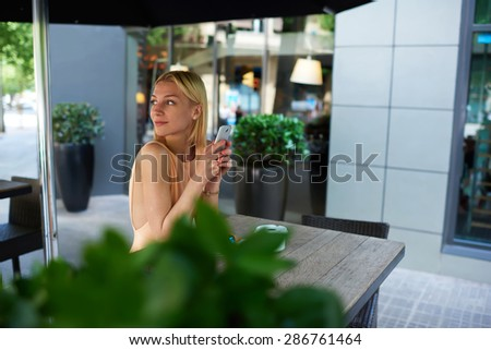 Gorgeous young woman typing message on mobile phone, pretty female connecting to wireless on telephone, successful businesswoman sitting at coffee shop with plants chatting and smiling dreamily - stock photo