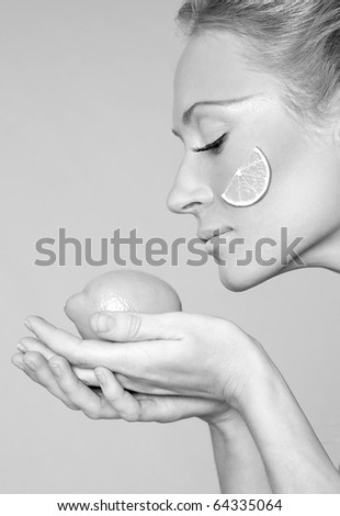 Gorgeous young woman wearing colorful make-up and holding slice of lemon - stock photo