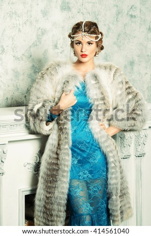 Gorgeous young woman wearing evening dress and beautiful furs. Luxury, rich lifestyle. Jewellery. Fashion shot. Interior in classical style.