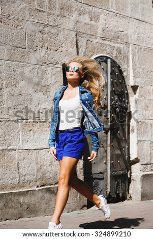 Gorgeous young woman, wearing in white shirt, blue jacket, shorts and sunglasses, posing in the jump near the gray concrete building, on the street of old city, full body - stock photo