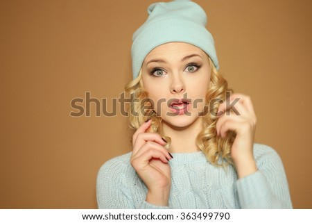 Gorgeous young woman with blond ringlets in a green knitted winter outfit smiling,over light brown - stock photo