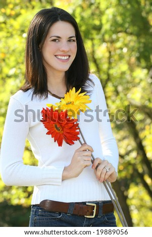 Gorgeous young woman with bright flowers outdoors in a park, forest - stock photo