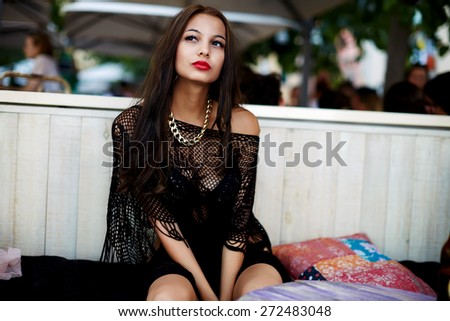 Gorgeous young woman with brunette long hair sitting at beach cafe, sensual female in bikini enjoying perfect summer day outdoors, fashionable girl relaxing in luxury place during her summer vacations - stock photo
