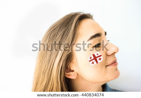 Gorgeous young woman with georgian flag on face closeup smiling - stock photo