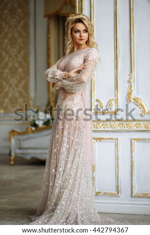 Gorgeous young woman with perfect makeup and hair style in luxury dress in interior