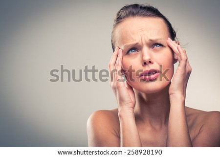 Gorgeous young woman with severe headache/migraine (color toned image) - stock photo