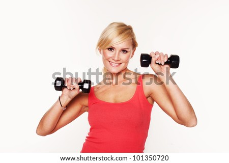 Gorgeous young woman working out with hand weights to keep her slim figure shapely. - stock photo