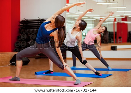 Gorgeous young women practicing yoga and performing an extended side angle pose - stock photo
