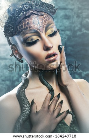 Gorgon medusa in dungeon. Young woman with creative fantasy hairstyle and make up - stock photo