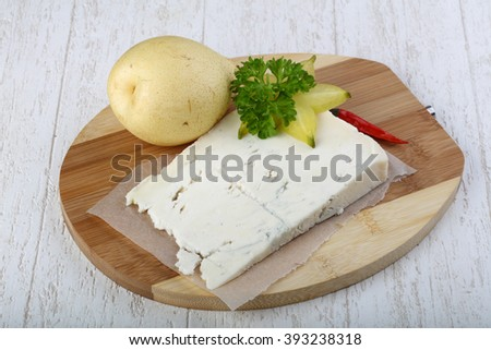 Gorgonzola cheese with pear and parsley on the wood background