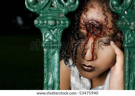 gory gunshot wound on beautiful woman behind a metal fence