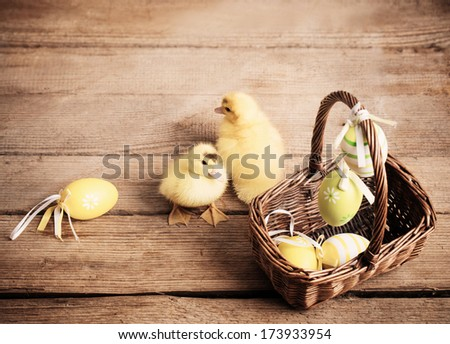 goslings with easter eggs on wooden background - stock photo
