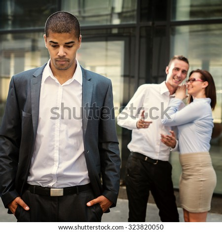 Gossip colleagues in front of their office, handsome businessman portrait in front and gossip out of focus in background. - stock photo