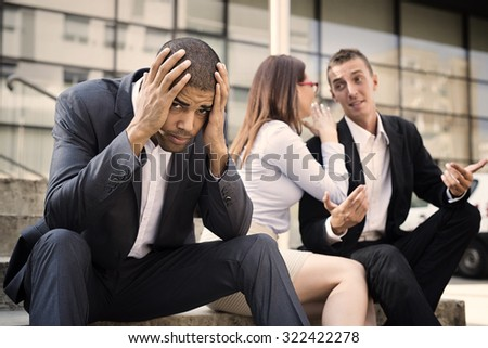 Gossip colleagues in front of their office sitting at stairs, handsome businessman portrait in front and gossip out of focus in background. - stock photo