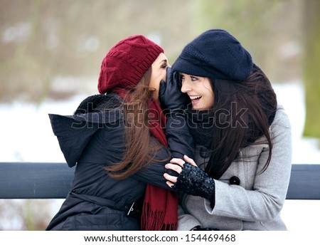 Gossip girl smiling in delight while listening to a secret outdoors - stock photo