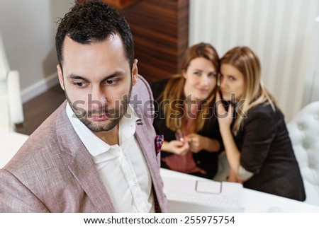 Gossip girls at office, handsome businessman portrait and gossip girls out of focus in background. - stock photo