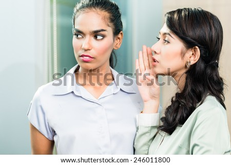 Gossip in the office, one woman whispering in ear of second business executive - stock photo