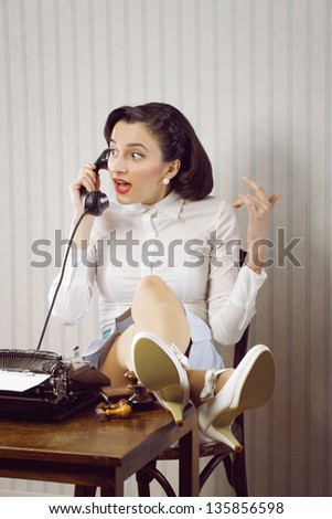 Gossip news, business woman talking on phone at desk - stock photo