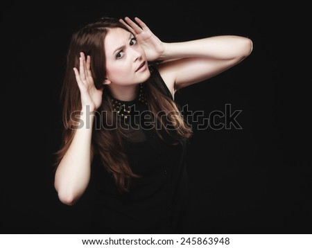 Gossip scandal or secrets. Young woman teen girl with hands to ear listening on black - stock photo