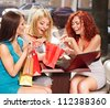 Gossip women with laptop in a cafe. - stock photo