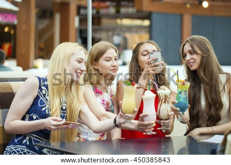 Gossiping by the cocktail. Close up four attractive young women drinking cocktails in shopping mall and having a talk with their friend