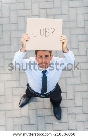 Got job? Top view of handsome young man in shirt and tie showing poster with job text message while standing outdoors - stock photo
