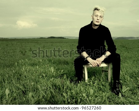 goth boy on a chair outdoors