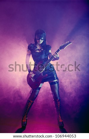 Goth girl in goggles plays guitar on the stage