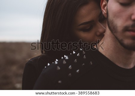 Goth girl kisses her boyfriend on the neck