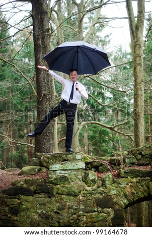 goth guy in business clothes dances with an umbrella