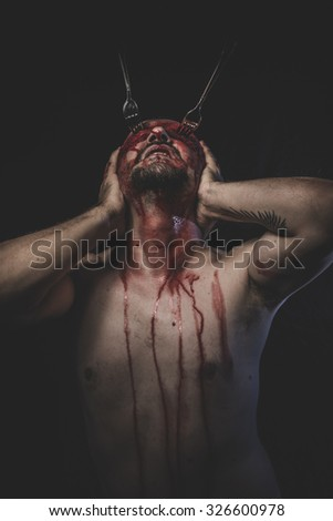 Goth, naked man with blindfold soaked in blood - stock photo